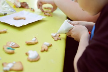 Close up on little kid decorating Christmas gingerbread