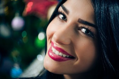 portrait of young beautiful brunette woman happy smiling & looking at camera on Christmas tree background