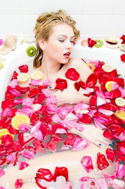 pure pleasure in luxury spa: portrait of eyes closed sexy hot pinup girl with blonde hair taking relaxing bath with flower petals on white copy space background
