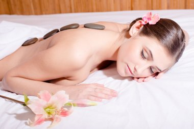 sleeping beauty: portrait of sexy young pretty woman with eyes closed during spa procedures stone therapy massage & aromatherapy on white bed background