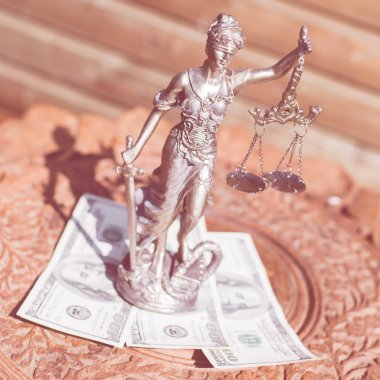 money and justice: sculpture of themis, femida or justice goddess standing on money bribe symbol of corruption