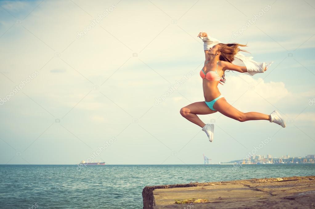 Amazing dancer in swimwear jumping up high on beach