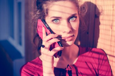Beautiful young woman talking on mobile cell phone with shadow from window blinds, closeup portrait