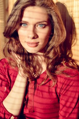 Beautiful young blue eyes lady with shadow from window blinds, closeup portrait