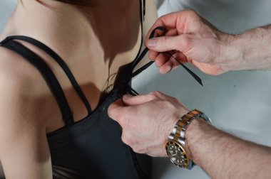 Close up mans hands  tie ladys corset in a bow