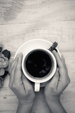 Black and white picture of hands embracing cup of coffee