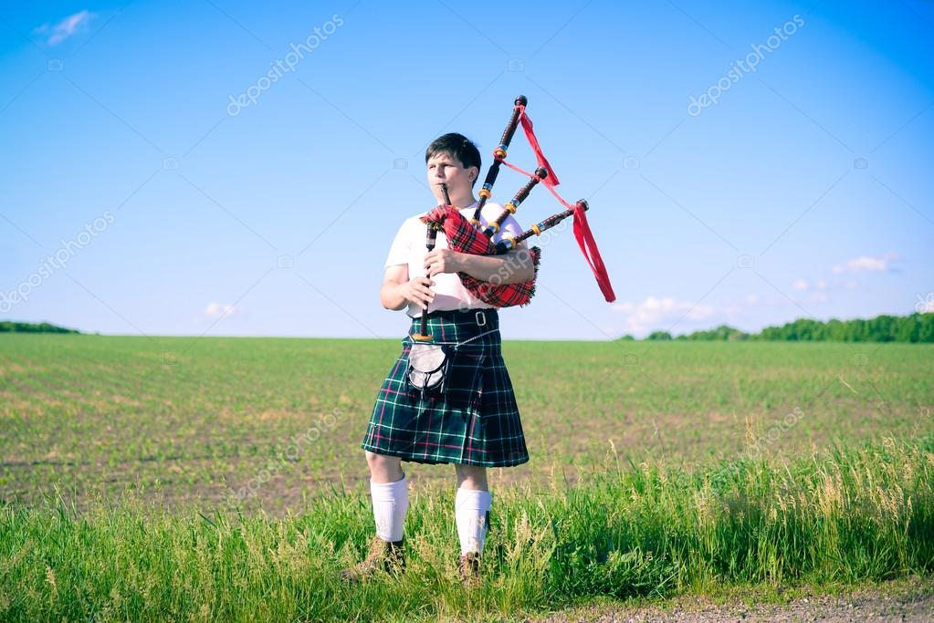 Portrait of man enjoying playing pipes in Scottish traditional kilt on green outdoors copy space summer field background