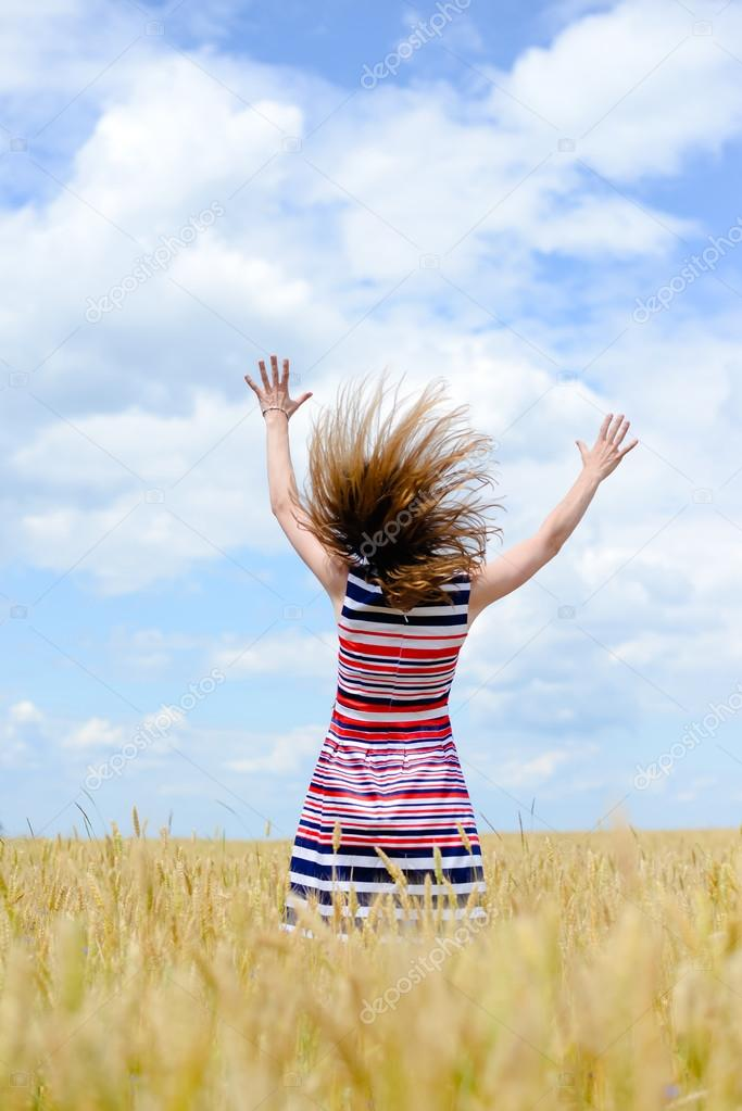 Image of one young pretty lady having fun standing in the field hands up on blue sky background copy space