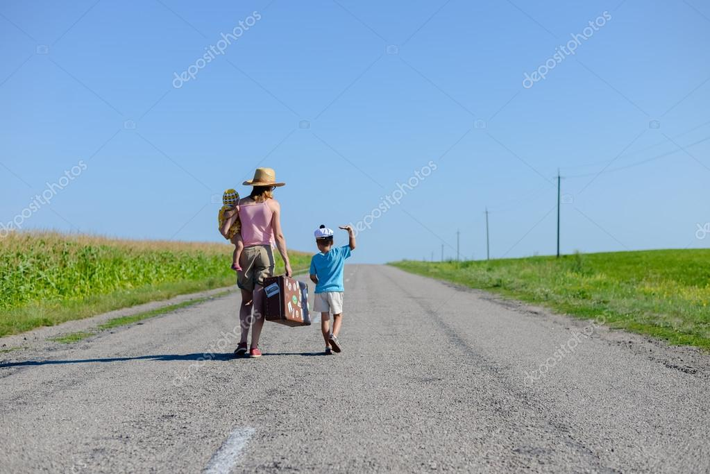 silhouette of female with kids walking on the countryside rural road on sunny blue sky outdoors background, copy space picture