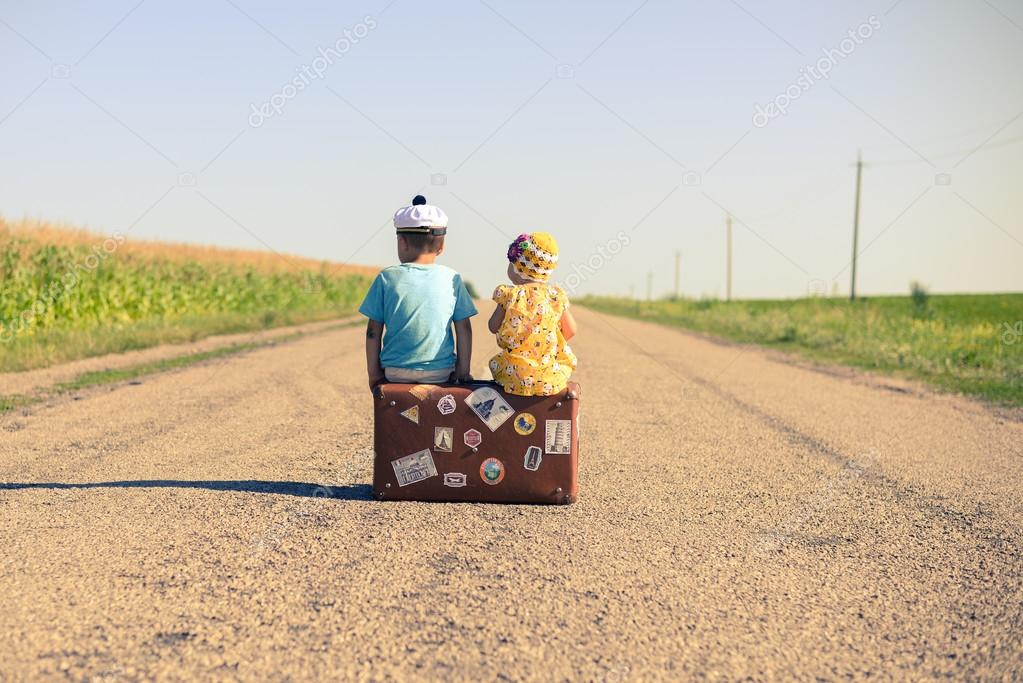 silhouette of kids sitting on the suitcase over countryside rural road on sunny blue sky outdoors background, copy space picture