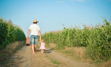 Man and babygirl walking away on road between corn field