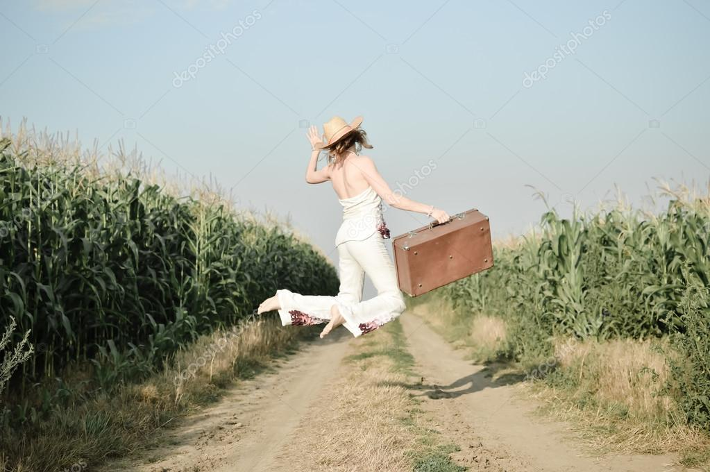Jumping girl wearing straw hat with suitcase in corn field