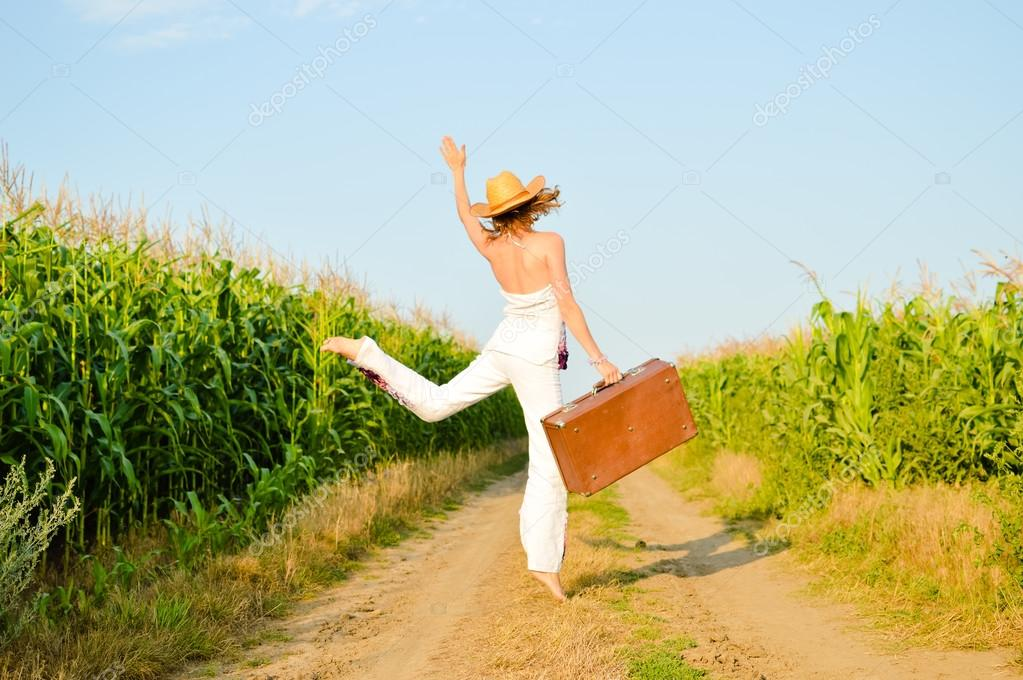 Jumping girl wearing hat with suitcase on road in field over blue sky outdoors background