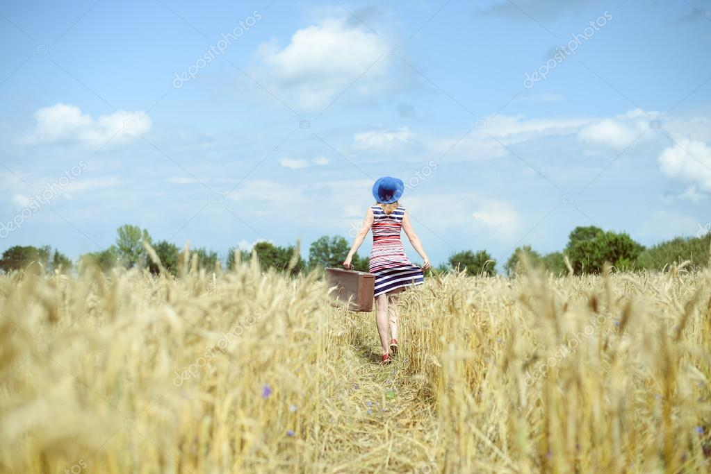 Woman wearing hat with suitcase walking away through wheat field