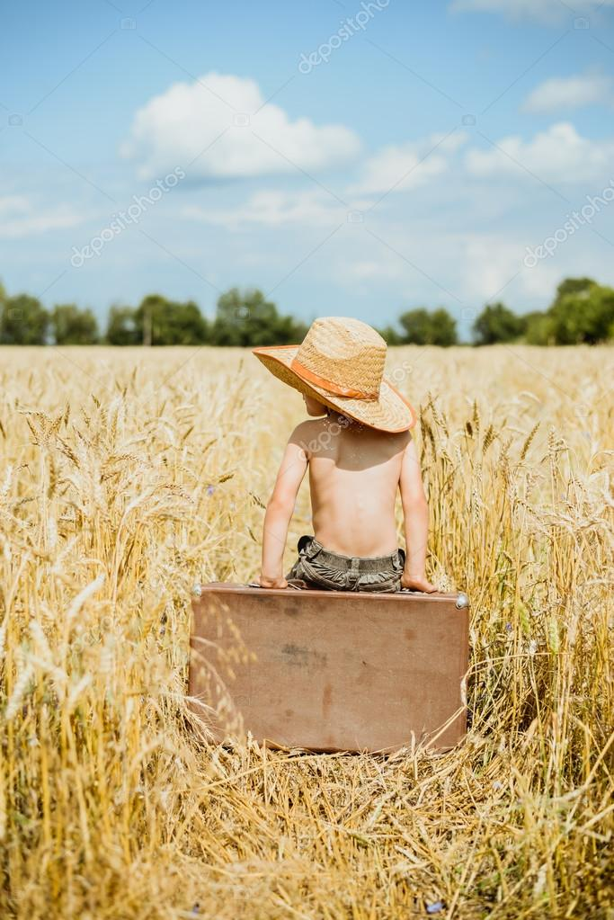 Little boy sitting on big old valize in summer countryside