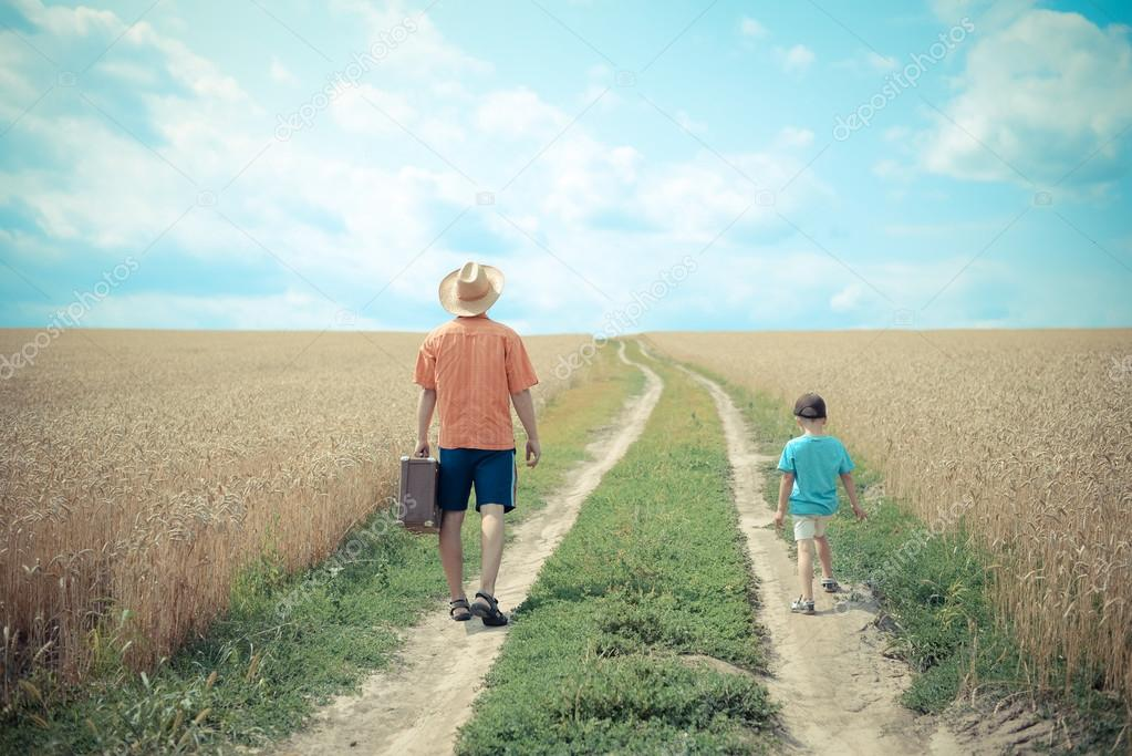 Man with valize and boy walking on road between field of wheat over sunny blue sky background