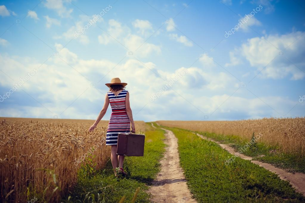 Woman wearing hat with suitcase on road in wheat field