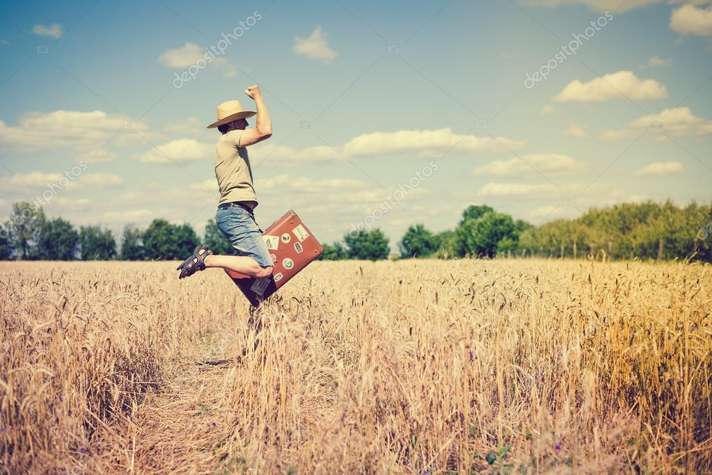 Jumping man wearing straw hat with suitcase in wheat field