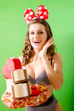 Excited girl wearing polka dotted bow and lingerie with gift boxes