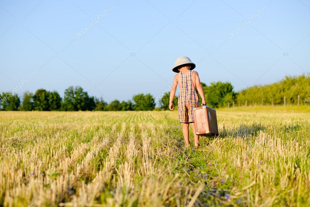 Little boy walking away carrying big old suitcase in field