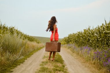 Picture of beautiful young lady on rural road holding suitcase in hand and walking on sunny day outdoors landscape background