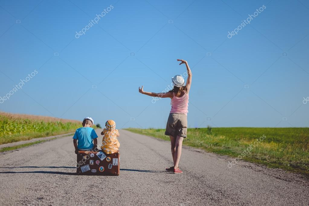 Young woman dancing near two children with suitcase on road