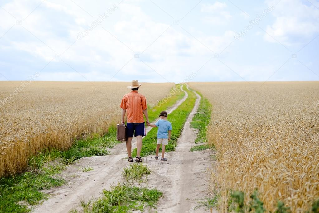 Man with suitcase and boy walking away in wheat field