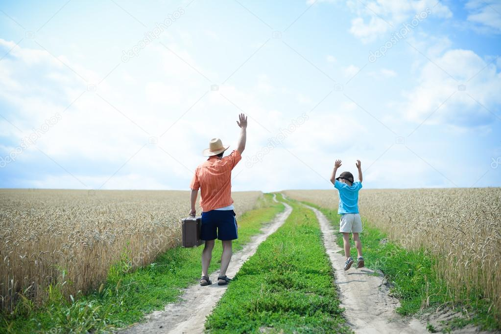 Travelling man and boy with old suitcase on country road