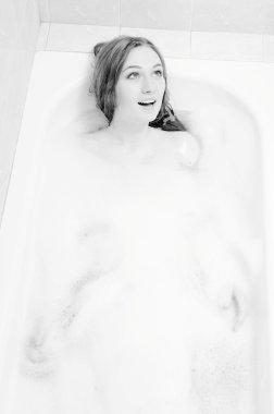 Picture of beautiful young woman relaxing in bath with foam having fun singing