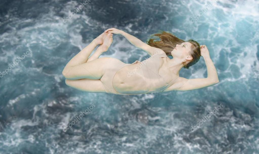 Beautiful woman floating in swimsuit on blue stormy underwater background