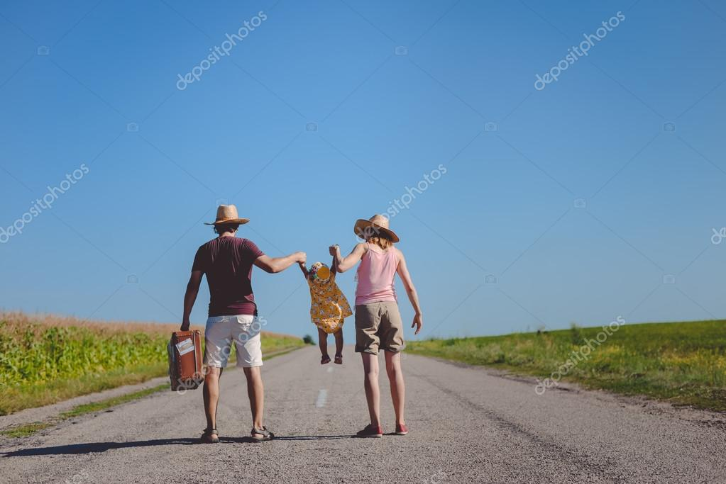 Parents swinging babe girl on countryside highway in sunny summer