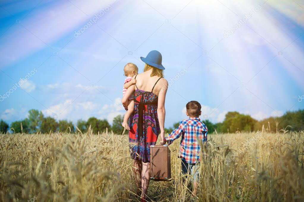 Image of woman wearing hat with baby girl walking away on wheat field.