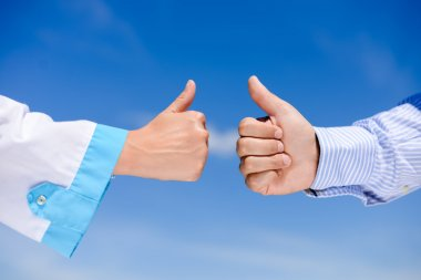 Thumb up between doctors over blue sky sunny outdoors background, closeup picture