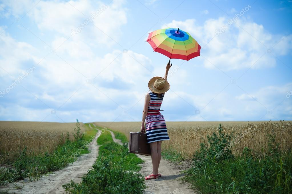 Image of young female with rainbow umbrella and old suitcase on countryside road on summer cloud sky background.