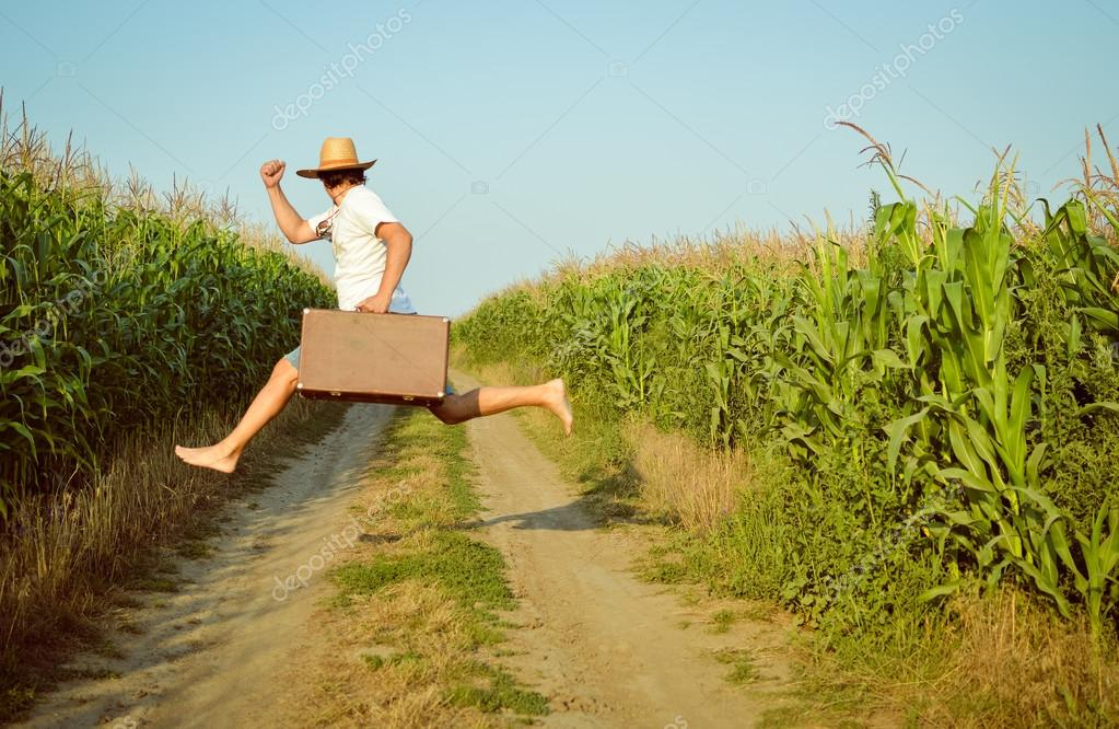 Rear view of man in straw hat enjoying his life jumping with suitcase on rural road.