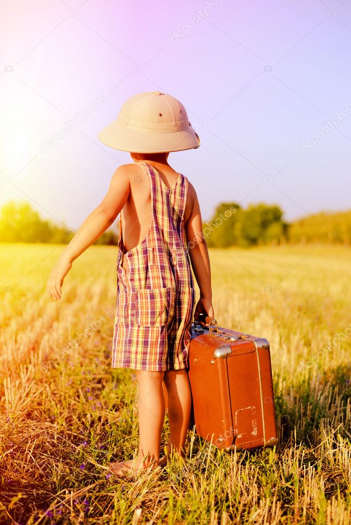 Picture of little boy wearing pith helmet and plaid romper carrying big valize in countryside on the blue sky outdoors