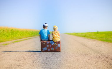Children on the suitcase over countryside rural road on sunny blue sky outdoors background, back view photography