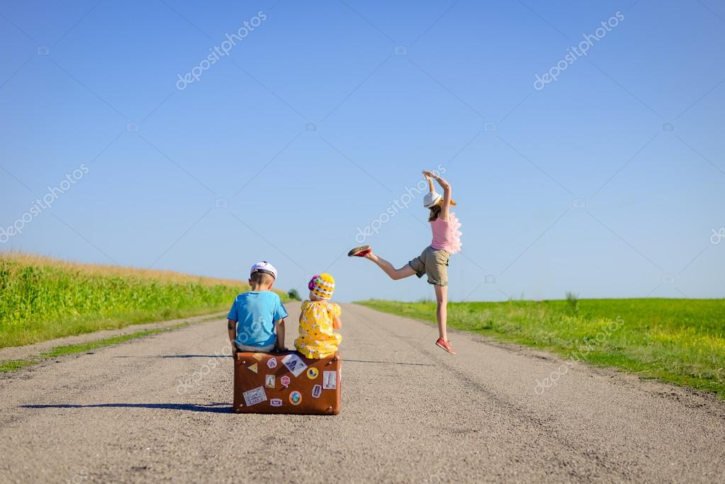 Image of excited woman jumping and two children sitting on old suitcase on country road.