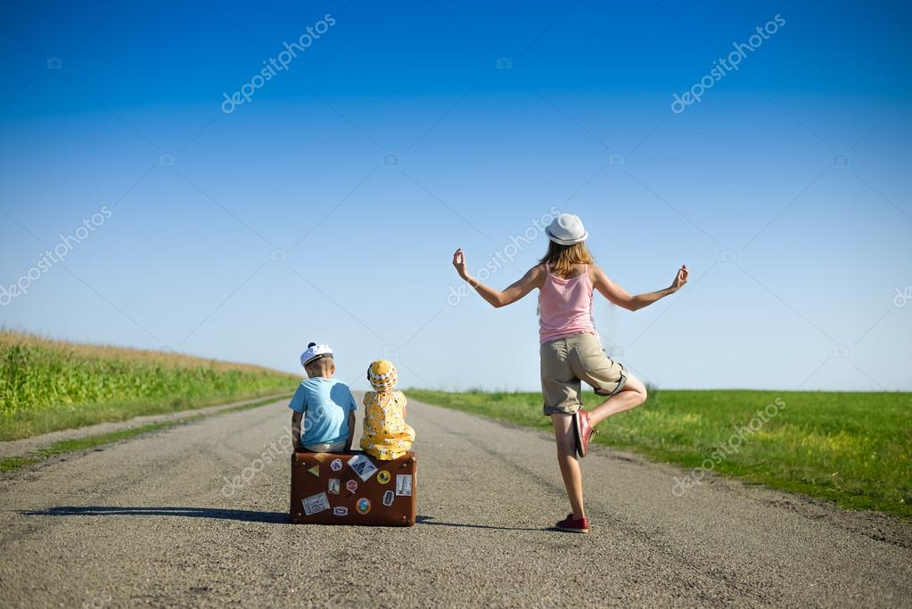 Young woman meditating near two children on summer country road