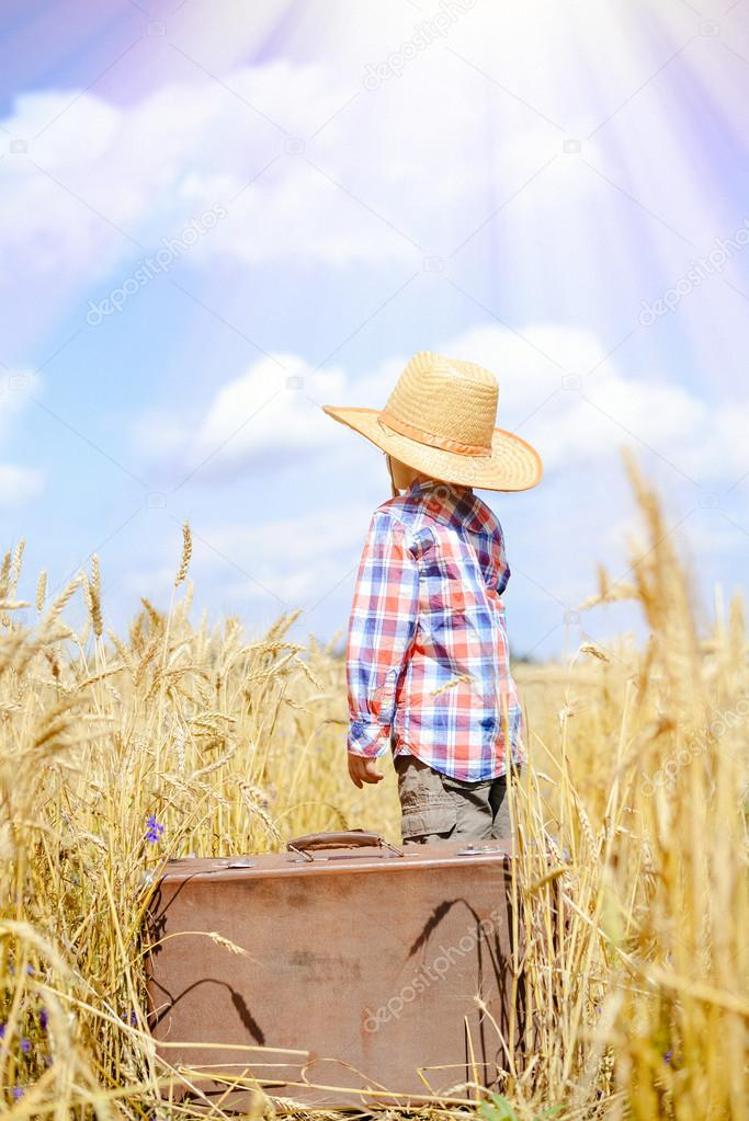 Boy wearing straw hat and plaid shirt with old suitcase