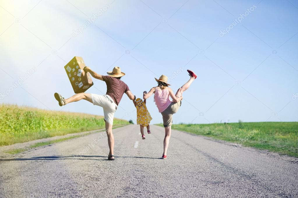 Happy family jumping and having fun on road in summer