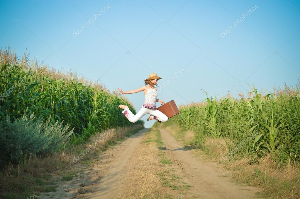Young girl jumping with suitcase on road in corn field