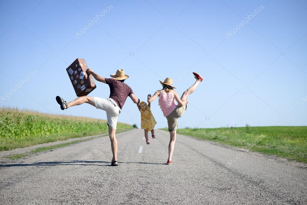 Parents and baby with suitcase jumping and dancing on road