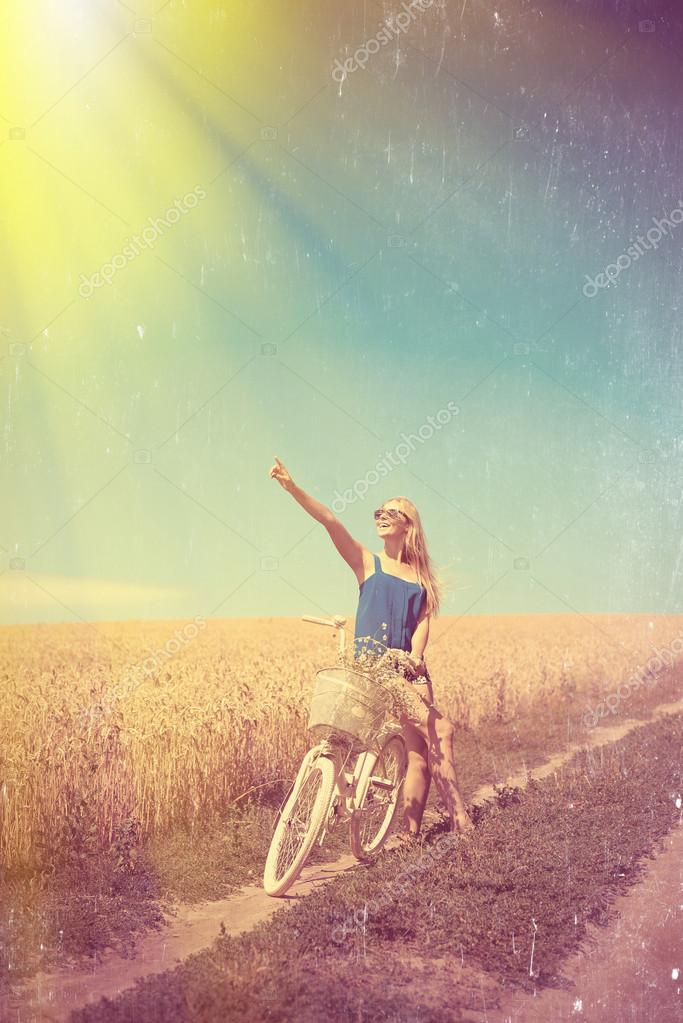 Sexy girl with white bike on sunny filtered countryside background.