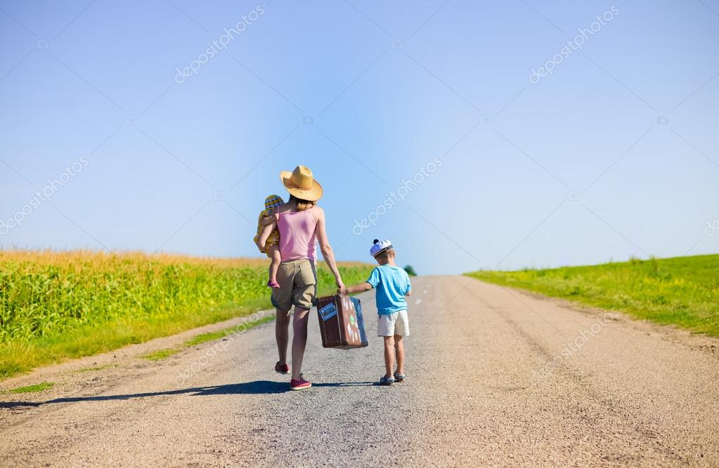 Family walking with old suitcase on sunny summer countryside road