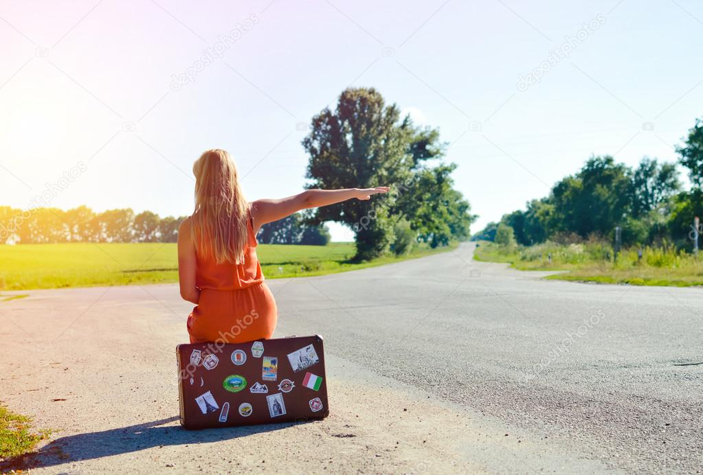 Young woman sitting on suitcase and hitchhiking car in countryside