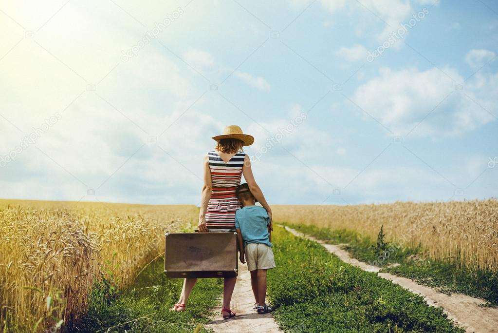 Woman and little boy standing in middle of country road