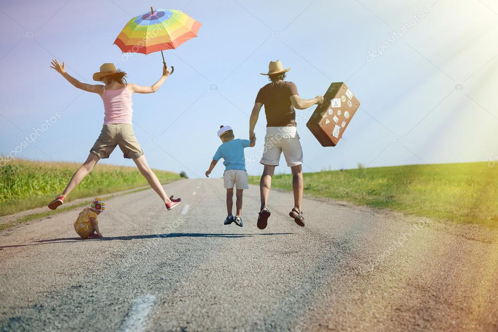 Happy family jumping with suitcase on country road in summer