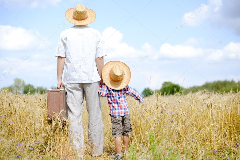 Picture of father and son travelling on summer wheat field and blue sky background