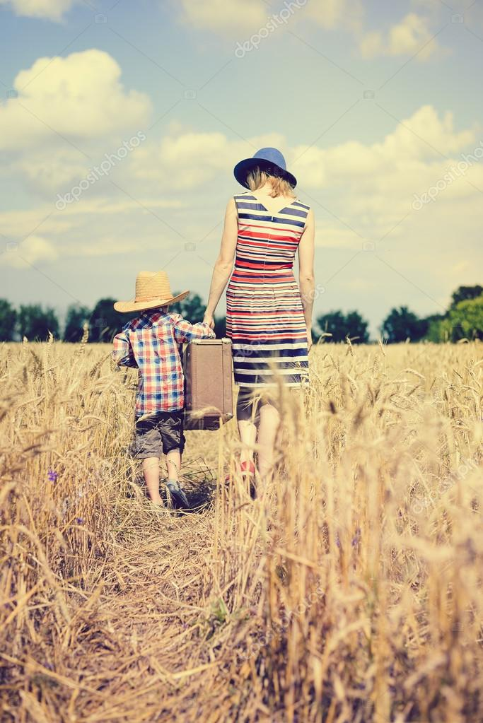 Mother and son walking along wheat field and carrying heavy suitcase